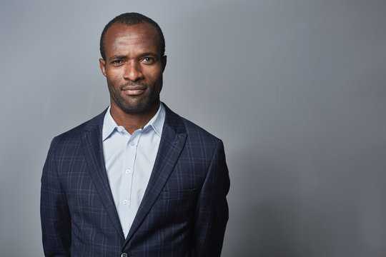 Confident look. Waist-up portrait of successful young african businessman is wearing in formal clothes and looking at camera assertively. Isolated background with copy space