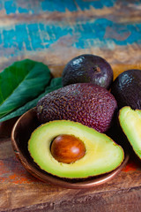 Healthy vegetarian food – green ripe avocado, new harvest, with leaves on stone plates with ornament