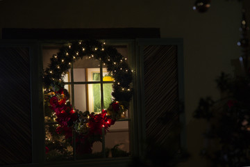Large holiday wreath on home window at night