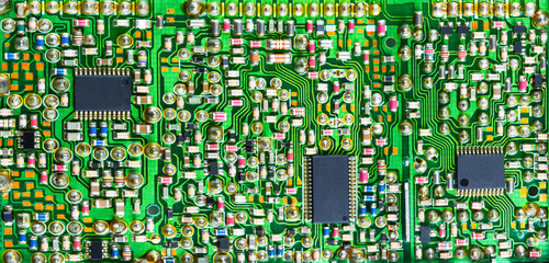Impressive printed circuit board with many electronic parts. Varied electrotechnical background with surface mount of components in green shade.