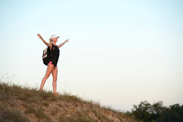 Young woman with hands up standing on the top of the mountain enjoying nice day. Travel, vacation, holidays and adventure concept.