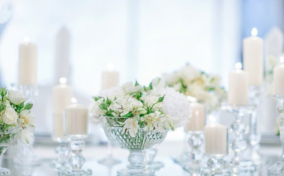 Fashionable decoration of a wedding banquet with white flowers. On the table are crystal vases with floral compositions