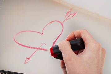 Women hand with red lipstick drawing heart and word love on mirror for Valentines day