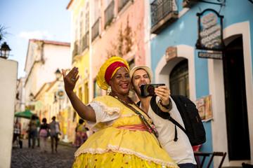 "Tourist taking selfie photos with Brazilian women ""Baiana"" in Pelourinho, Salvador, Bahia, Brazil"