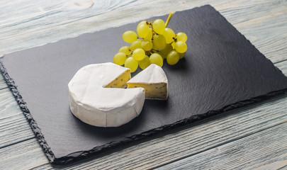Камамбер с виноградом на каменной доске черного цвета