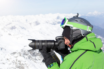 skier photographing mountain with professional camera