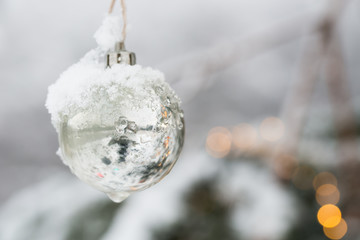 Schnee auf einer Weihnachtsbaumkugel  und Lichter Kerzen als Motiv zu Weihnachten