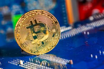 Golden Bitcoin Cryptocurrency on computer circuit board. Macro shot