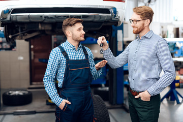 The man gives his car to the auto service. The client passes the keys to the car to the mechanic
