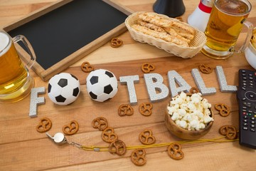 Remote control, slate, snacks, drinks and football word arranged