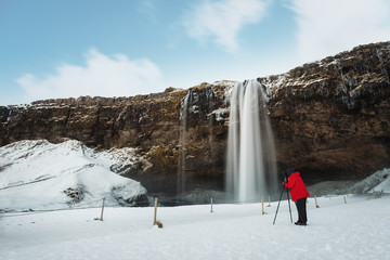 Winter waterfall landscape, photographer in red jacket taking photograph with camera tripod at Seljalandsfoss waterfall in Iceland