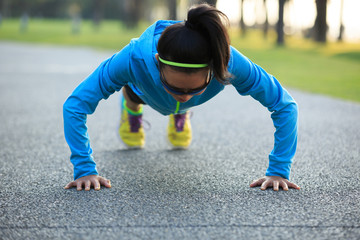 Young fitness woman exercising pushup at tropical park