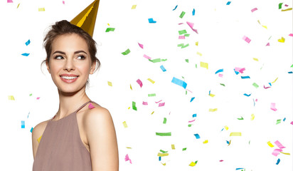 Happy smiling girl with festive hat on head and colored confetti on dress. Isolated on white background. Close up portrait of adorable laughing birthday girl.