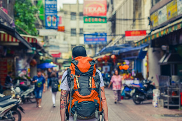Backpacker man walking in the street of Asia. Bangkok, Thailand.