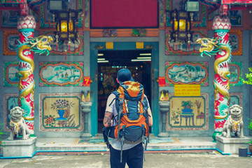 Backpacker man in chinese temple in the street of Asia. Bangkok, Thailand.
