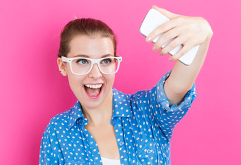 Young woman taking a selfie on pink background