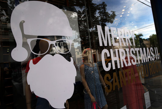 An image of Santa Claus next to a Merry Christmas sign is seen on a window shop in Buenos Aires