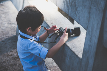 Cute Asian boy taking photo by digital camera outdoors