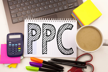 Word writing PPC - Pay per Click in the office with laptop, marker, pen, stationery, coffee. Business concept for Internet SEO Money Workshop white background with copy space
