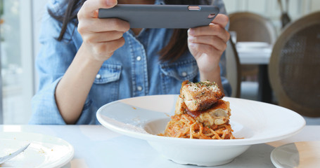 Woman taking photo on cellphone in restaurant for her dish