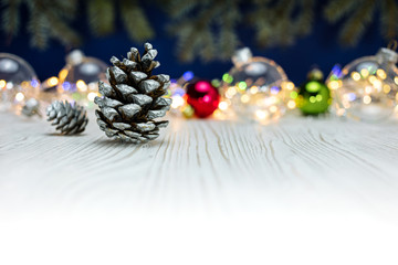 christmas background with pine cones, glass balls and colorful blurred festive holiday lights