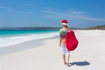 Christmas in Australia - woman walking along beach with festive santa hat in summer