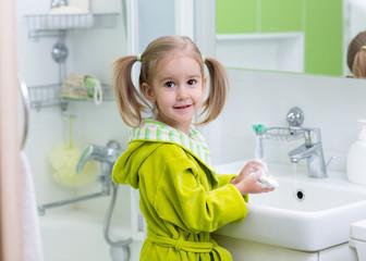 Happy kid or child brushing teeth in bathroom. Dental hygiene.