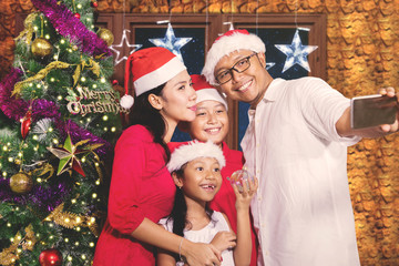 Young family taking picture near Christmas tree