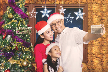 Parents with child taking photo near Christmas tree