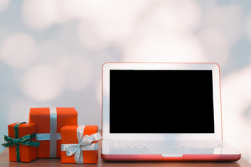 Christmas, new year, presents box and laptop computer mockup on wooden table over bokeh wall background and copy text space for writing messages