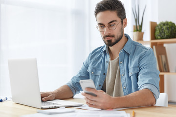 Stylish bearded male freelancer works remotely at home, uses modern electronic devices and internet connection, being always in touch, recieves messages and keyboards on computer. Technology, people