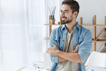 Glad handsome creative young male designer wears fashionable clothes, looks with smile aside, tries to get interesting idea for new project, stands in his cabinet, being inspired by something.
