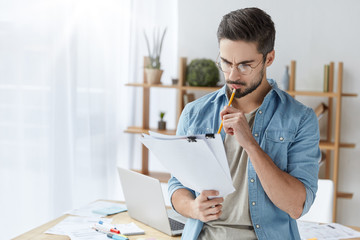 Young male executive officer has attentive look at documents, reads details of agreement, studies contract with focused expression, holds pencil. Fashionable man works on creating annual report