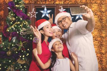 Asian family taking photo near Christmas tree