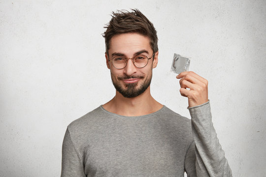 Curious bearded male holds new kind of condom, wonders about its quality, wears casual grey sweater, stands against white concrete wall. Handsome young man advertises product of contraception