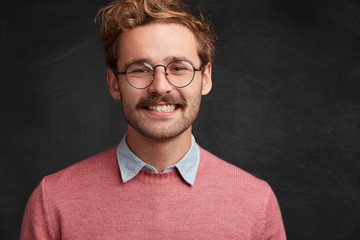 Headshot of cheerful smiling male has stylish hairdo, wears glasses, elegant clothes, glad to hear good news about his promotion. Satisfied male model rejoices achievement and reaching goals