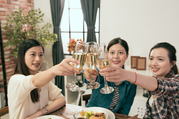 women hands holding glasses and toasting up