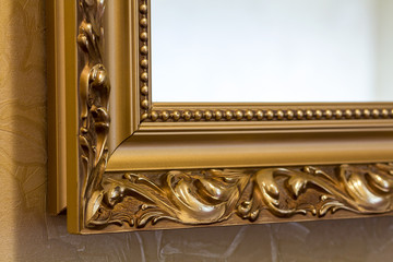 Part of the ornate, golden color carved mirror frame in ancient style.