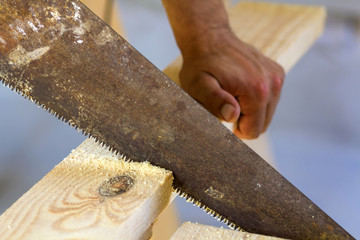 Carpenter hand with saw cutting wooden boards