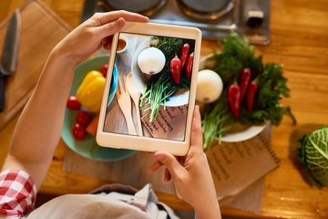 Close-up shot of female food blogger taking picture of ingredients necessary for preparing healthy dish on digital tablet while standing at kitchen table
