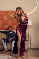 Picture of dancing blonde in home dress and men in dressing gown