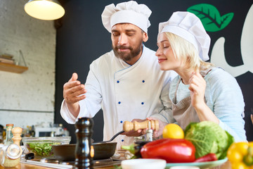Experienced bearded chef and his attractive young assistant enjoying smells coming from frying pan while preparing delicious dish at restaurant kitchen