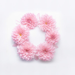 Round frame of pastel pink flowers on white desk background. Floral wreath. Layout for holidays greeting of Mothers day, birthday, wedding or happy event
