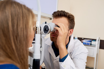 Portrait of young ophthalmologist testing sight of female patient using slit lamp exam n eye clinic