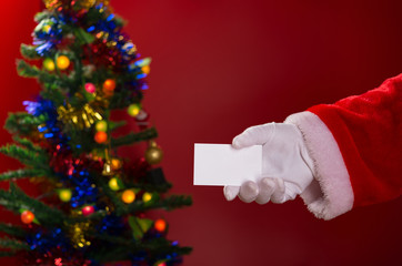 Santa Claus holding a white blank card good for text with decorated Christmas tree on background