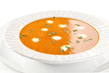 Tomato soup with cream on white background