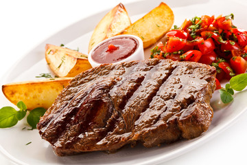 Grilled steak, baked potatoes and vegetable salad on white background