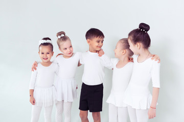 Cute little kids dancers on white background. Choreographed dance by a group of small ballerinas practicing at a classical ballet school