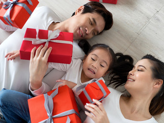 Happy Asian family with giftboxes lying on the floor