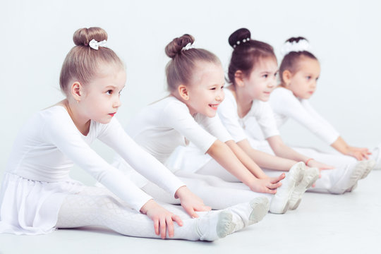 Group of graceful pretty little ballerinas practicing during class at a classical ballet school their first choreographed dance